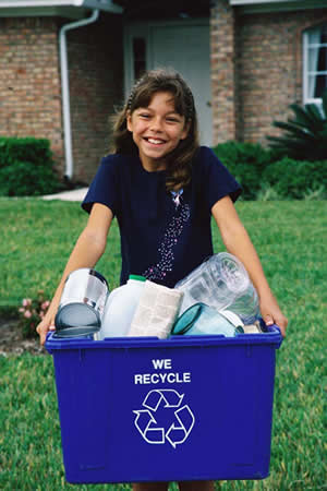 girl carrying recycling bin in front of house
